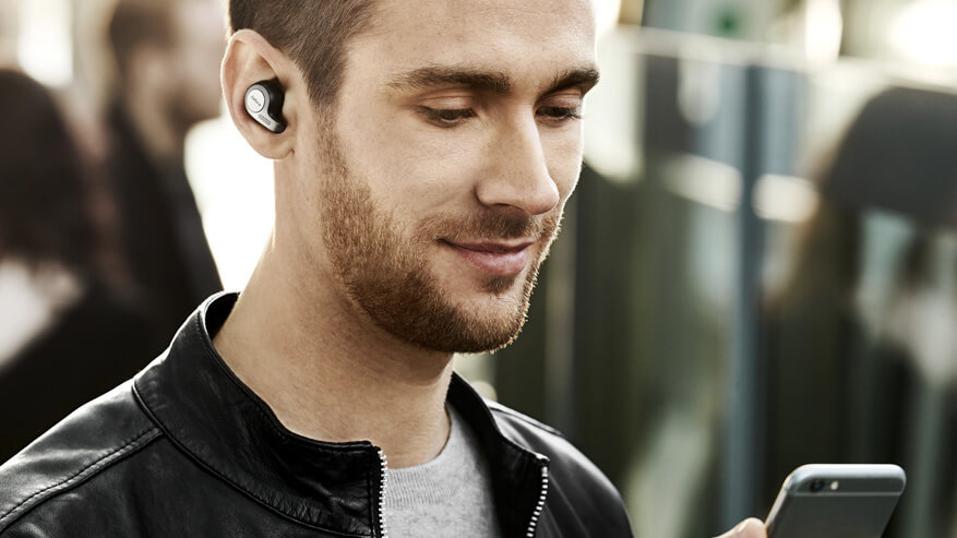 Man wearing Jabra Elite 65t true wireless earbuds while commuting